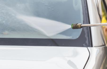 Вода под напором льется на лобовое стекло автомобиля